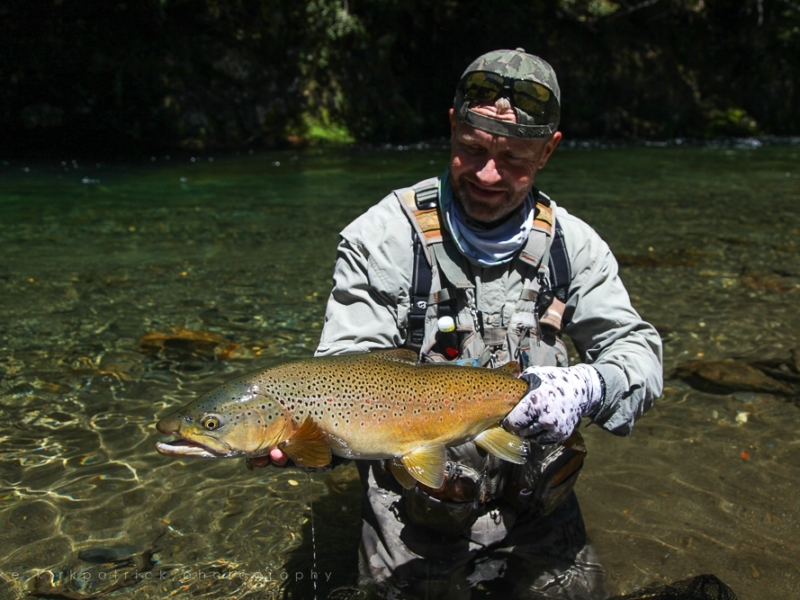 Angler holding a brown trout guided by Mike Kirkpatrick